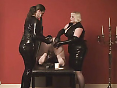 Wicked babes in latex fuck a thrall with dildos